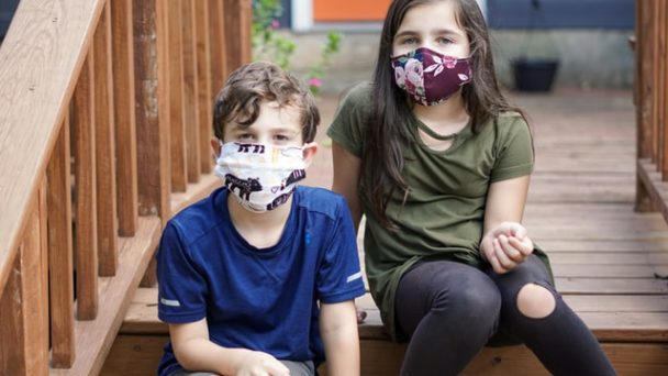 Bambini seduti sulle scale con mascherina per corona virus