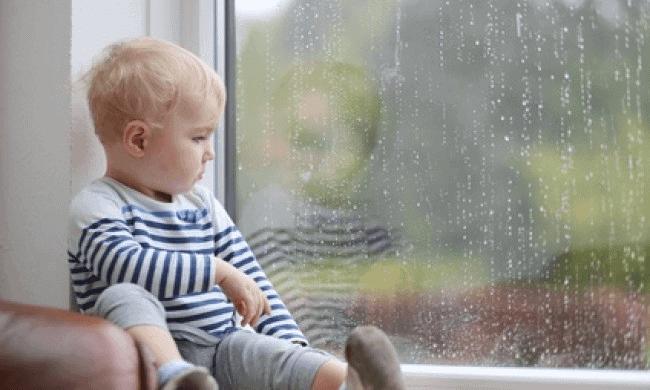 Pioggia: bambino triste che guarda la pioggia