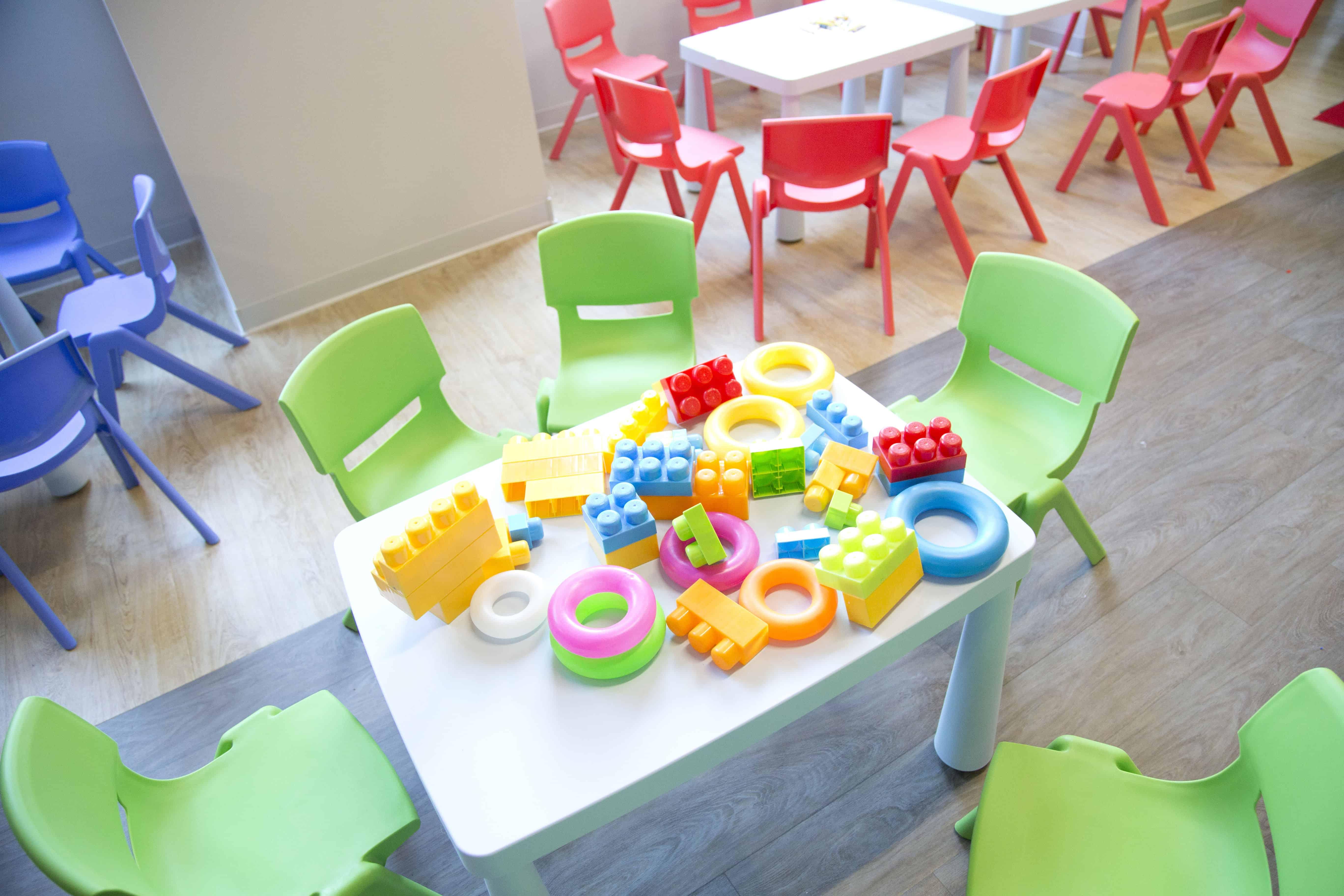costruzioni colorate sul tavolino dei bambini con intorno le sedioline